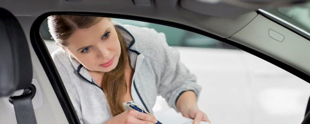 Kobieta spisuje stan licznika samochodu